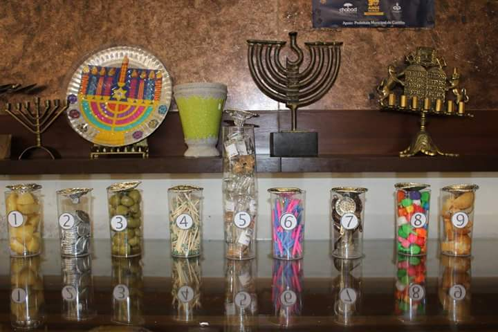 Guess how many. Menorah with chanukah objects (matches, candles, coins, dreidels, potatoes, oliv ...